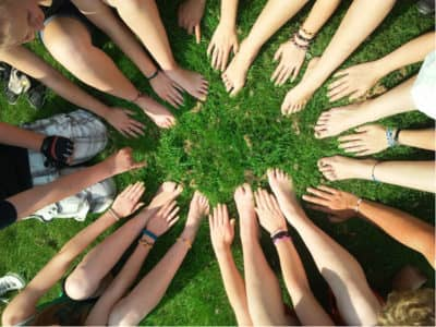 Group of people putting hands together in a circle.